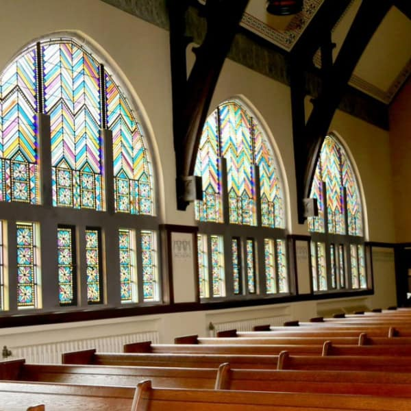 Interior of our church with the stained glass windows as a focal point