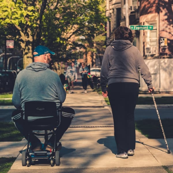 An elderly couple with one in a wheelchair and one with a walking cane