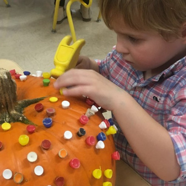 First Congo Preschooler decorating a pumpkin