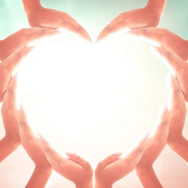 Multiple hands forming the shape of a heart