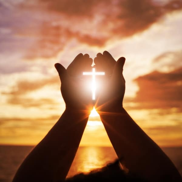 Hands reaching towards sun while holding a cross
