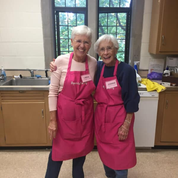 Two happy woman hugging in a kitchen
