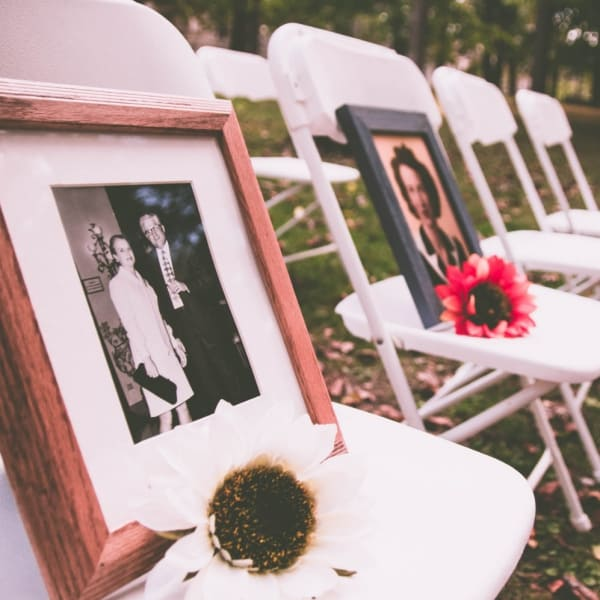 Family photos with flowers on chairs at a memorial service