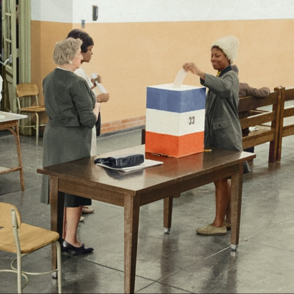 A woman casting her vote at a ballot booth
