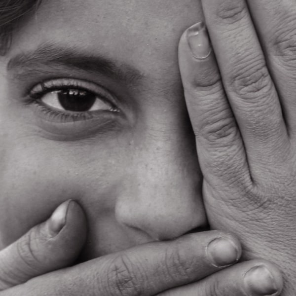 A refugee woman covering her face with her hands