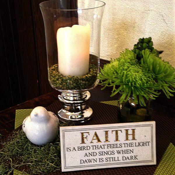 A candle on a table with a Faith card