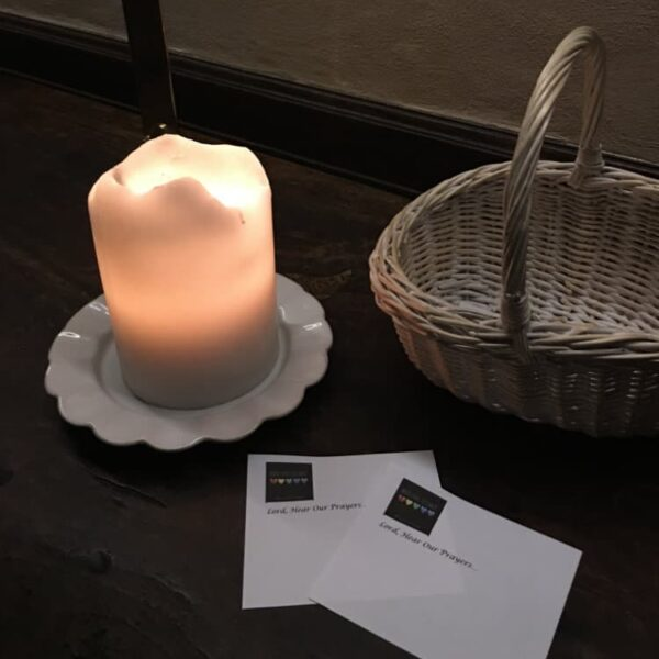 A lit candle on a table with notecards