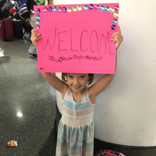 Girl holding a pink welcome sign for First Congo visitors
