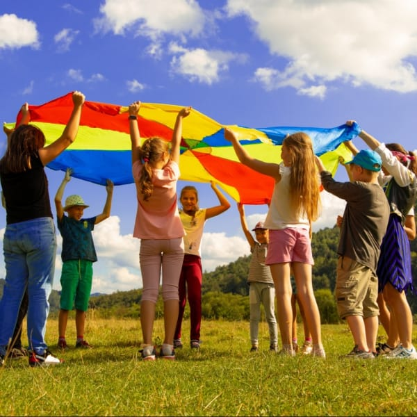 Kids playing with a huge kite outside